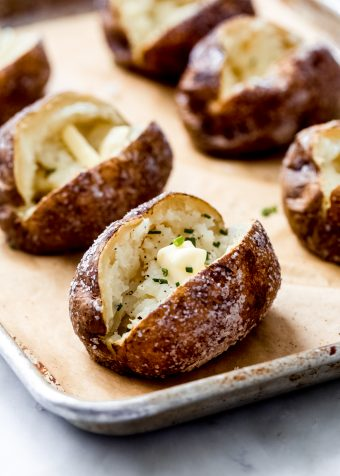 freshly baked potatoes on a sheet pan with butter and chives