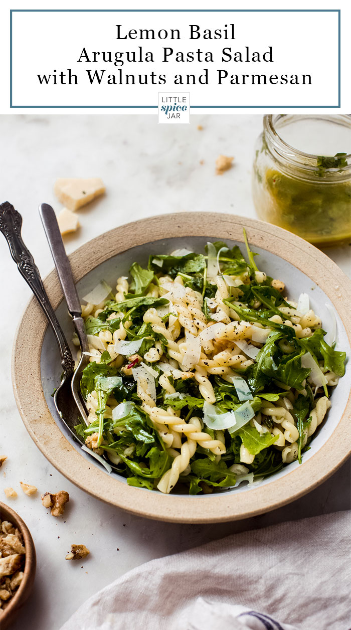 prepared lemon basil arugula salad with parmesan cheese in a bowl with serving utensils