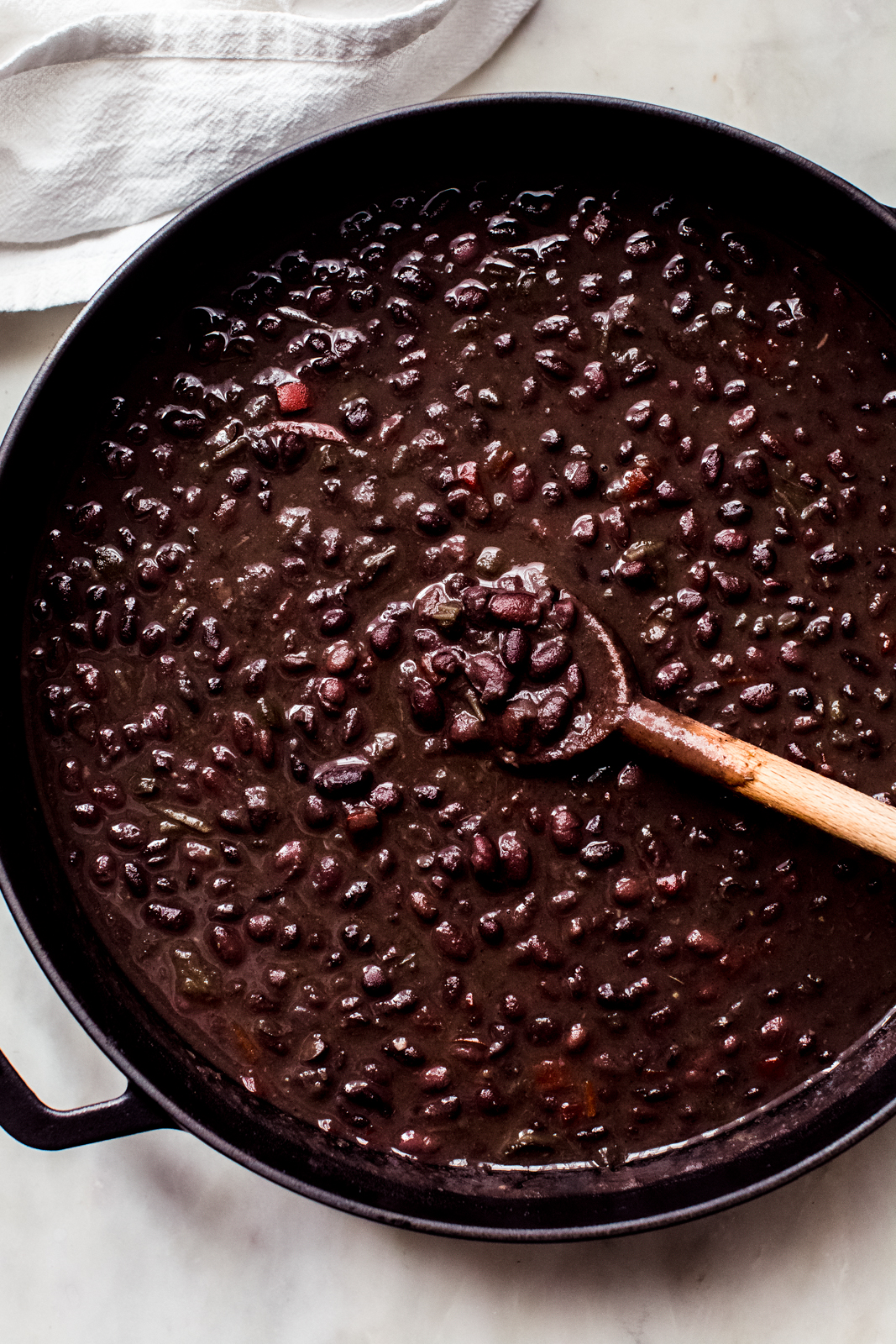 simmered cuban black bean soup in cast iron pot with wooden spoon