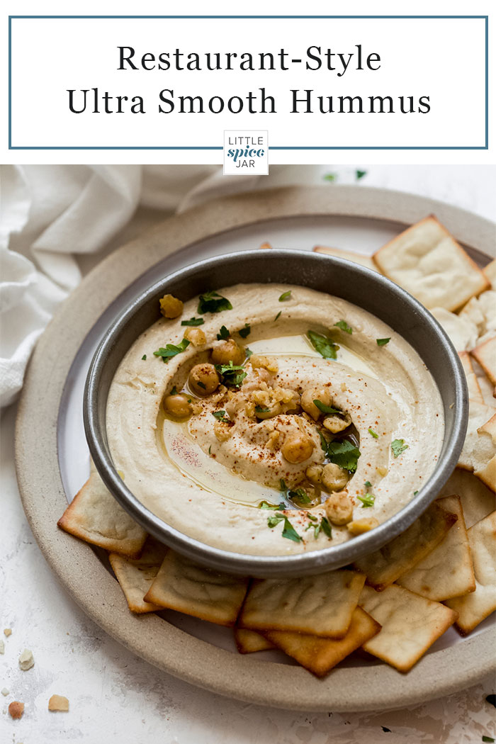 bowl of hummus with a swirl surrounded by a plate of pita chips