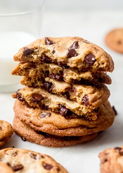 stick of chocolate chip cookies with broken halves showing inside texture on marble