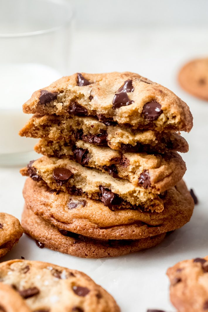 stack of chocolate chip cookies with broken halves showing inside texture on marble