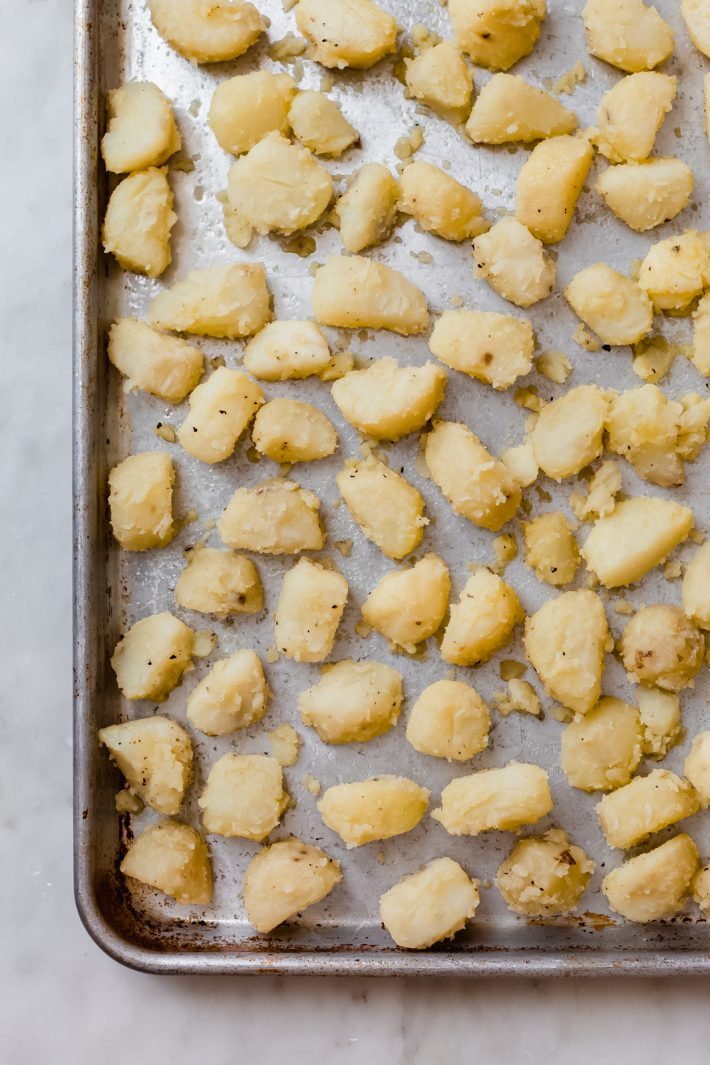 parboiled potatoes spread on sheet pan ready to roast