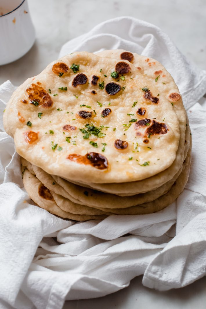 stack of garlic naan brushed with garlic butter on flour sack towel