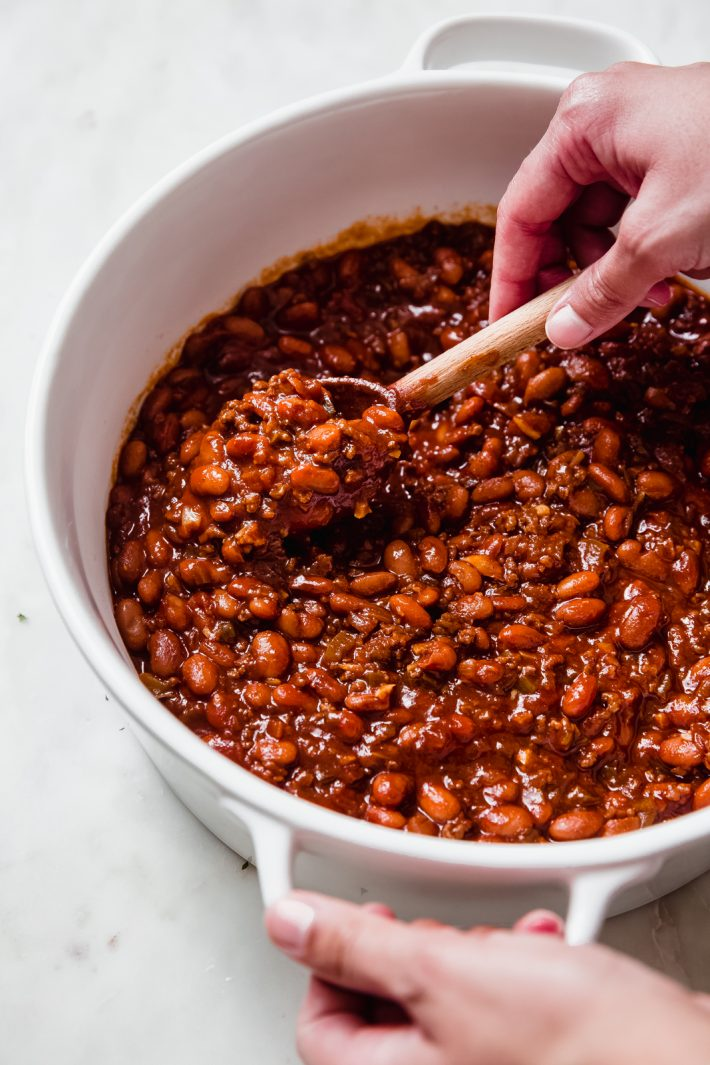 hand with wooden spoon filled with baked beans scooped from dish