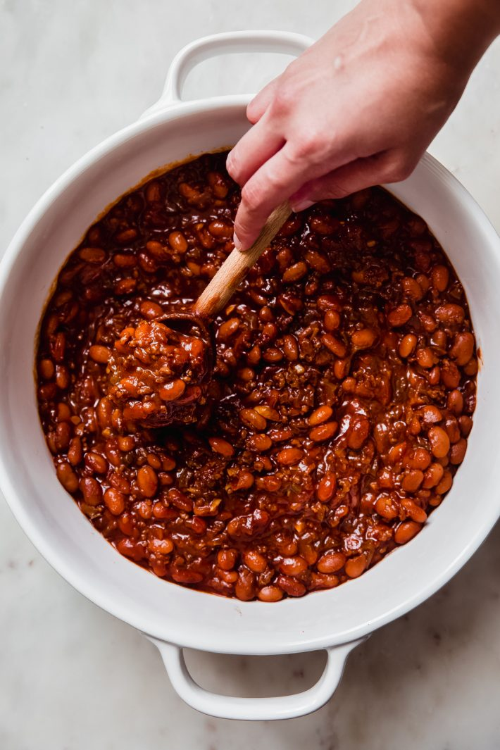 wooden spoon being lifted by hand filled with baked beans