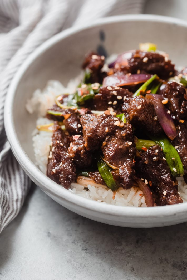 close up shot of crispy beef with sesame seeds and scallions on jasmine rice