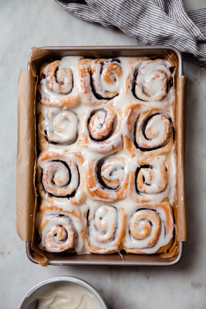 prepared cinnamon rolls in a baking dish on white marble surface