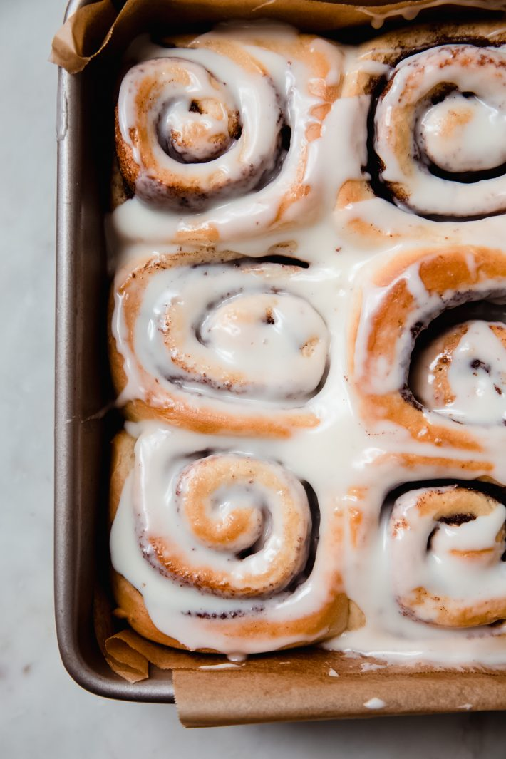 prepared cinnamon rolls in baking pan topped with cream cheese icing