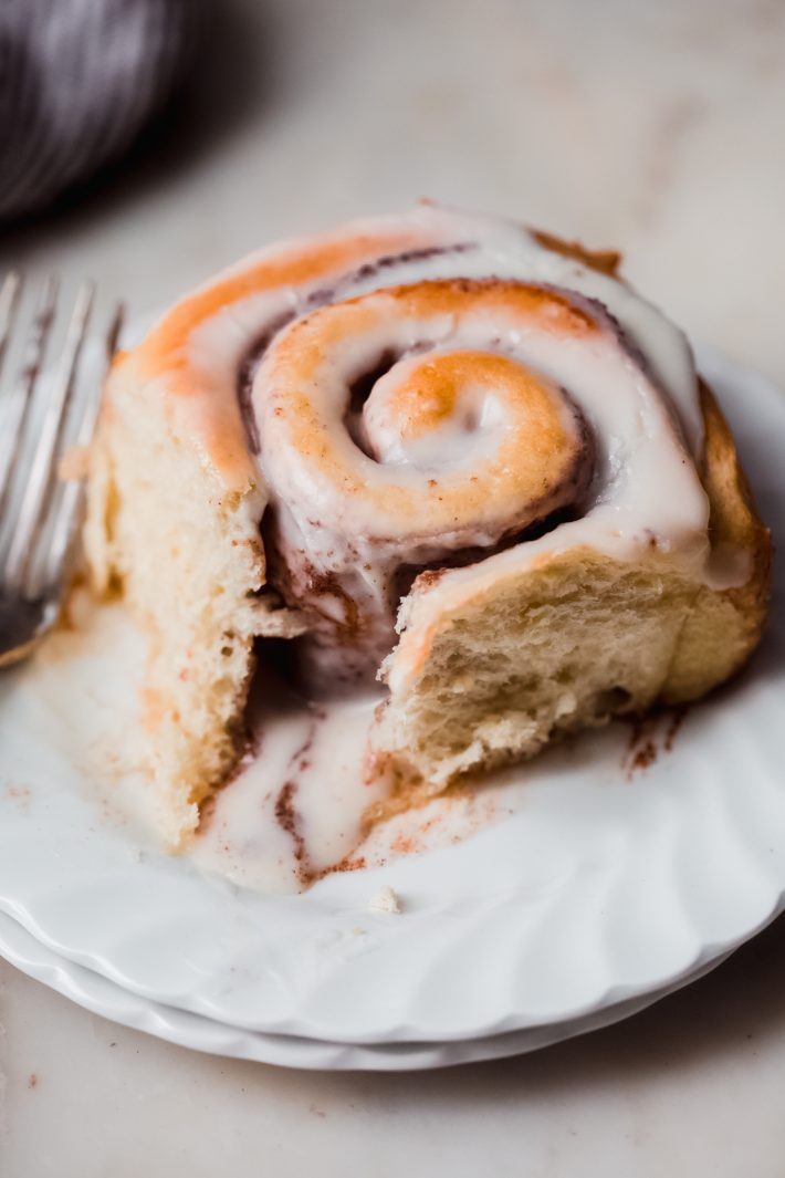 warm baked swirled cinnamon roll with icing on a white plate with fork