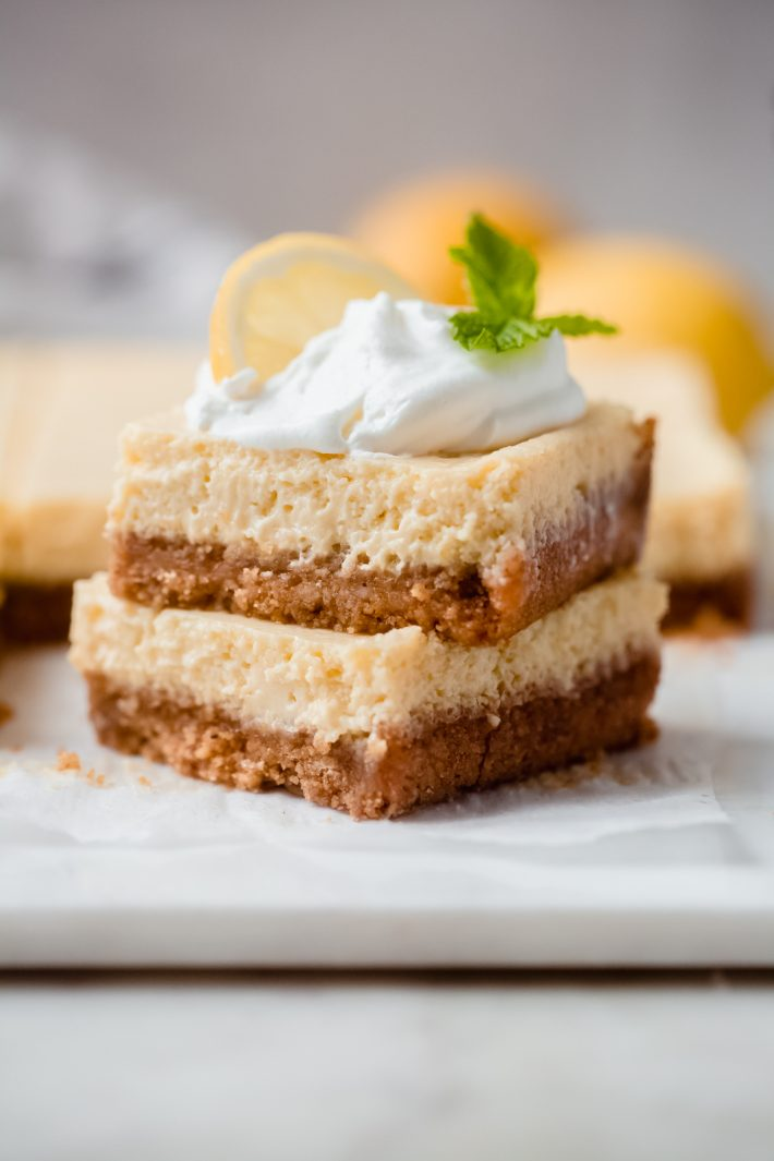 stack of two creamy lemon squared topped with whipped cream, a lemon slice, and a sprig of mint