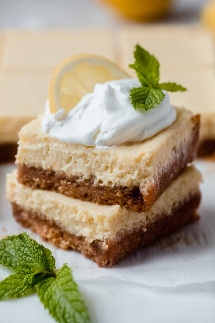 stack of two lemon squares with whipped cream, sprig of mint, and a lemon slice