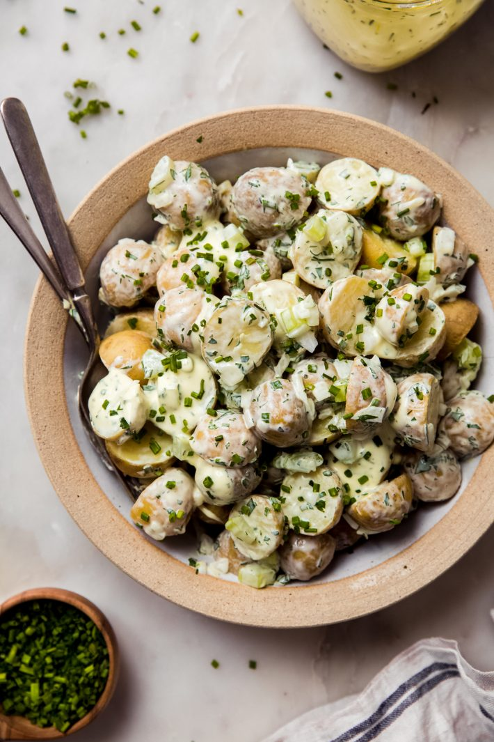 sour cream chive potato salad in dish with fork and spoon on white marble surface