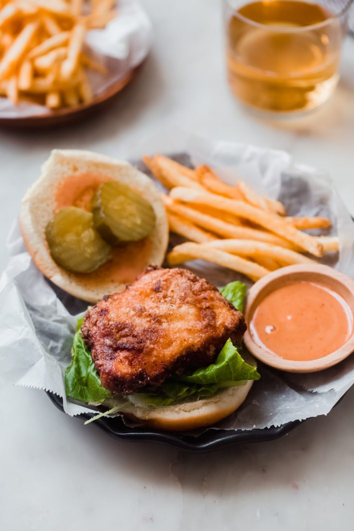 open face crispy chicken sandwich on plate surrounded by top bun, fries, and homemade sauce