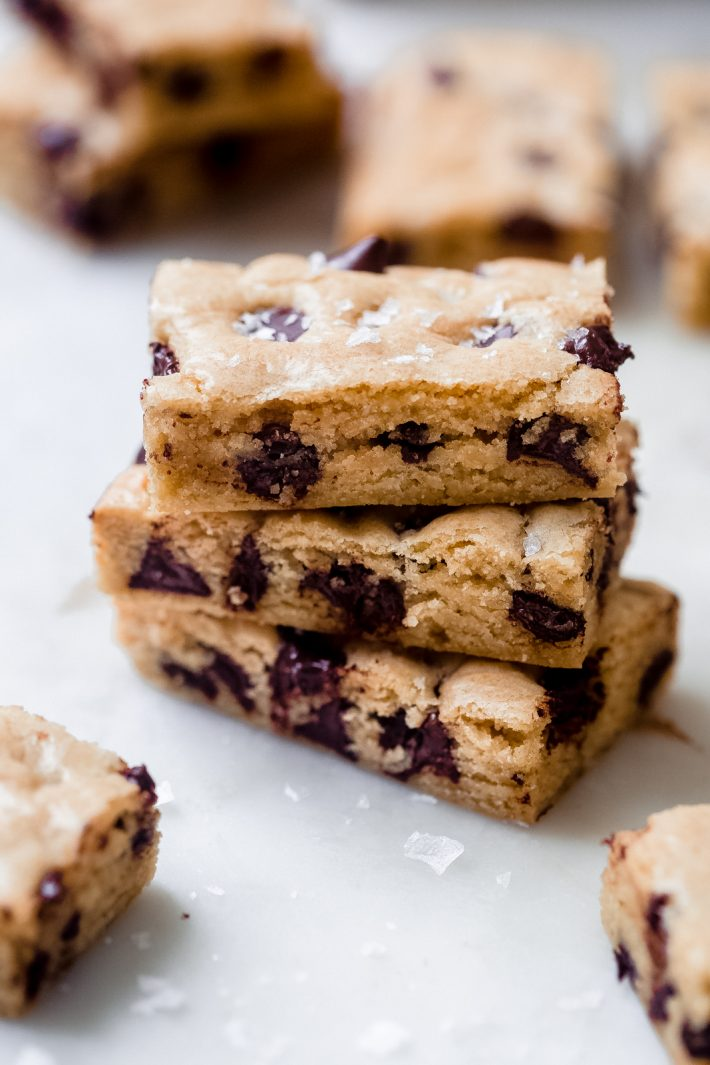 three chocolate chip cookie bars sprinkled with flaked sea salt on white marble surface