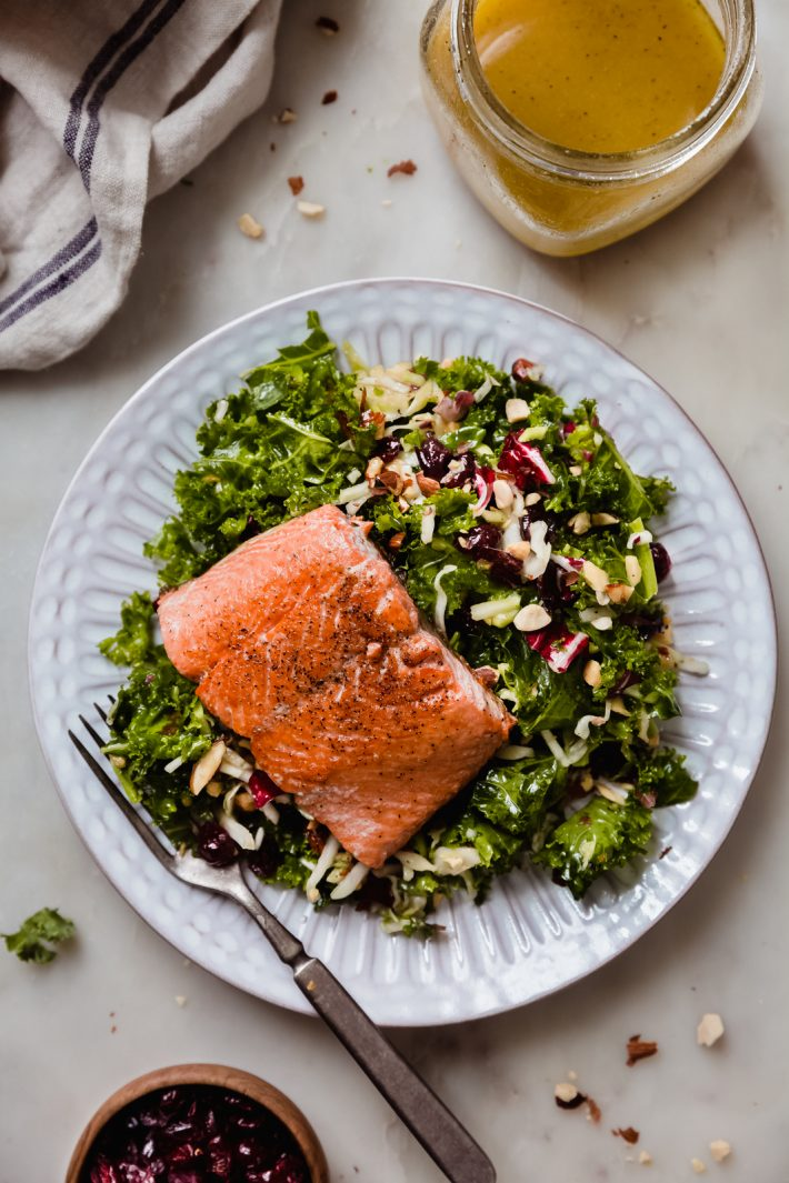 kale salad dressed with vinaigrette and cranberries topped with pan seared salmon