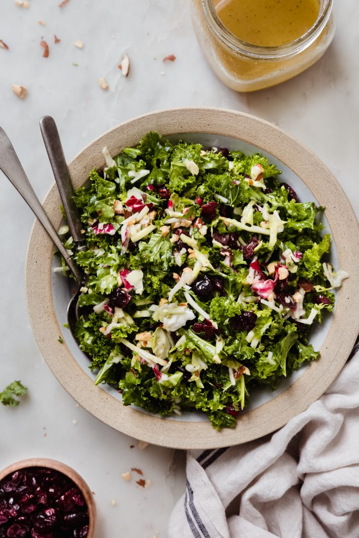 rimmed plate with serving spoon and fork filled with prepared kale crunch salad on white marble