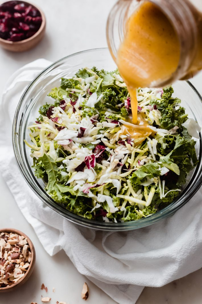 pouring prepared vinaigrette into kale and cabbage salad mix in glass bowl