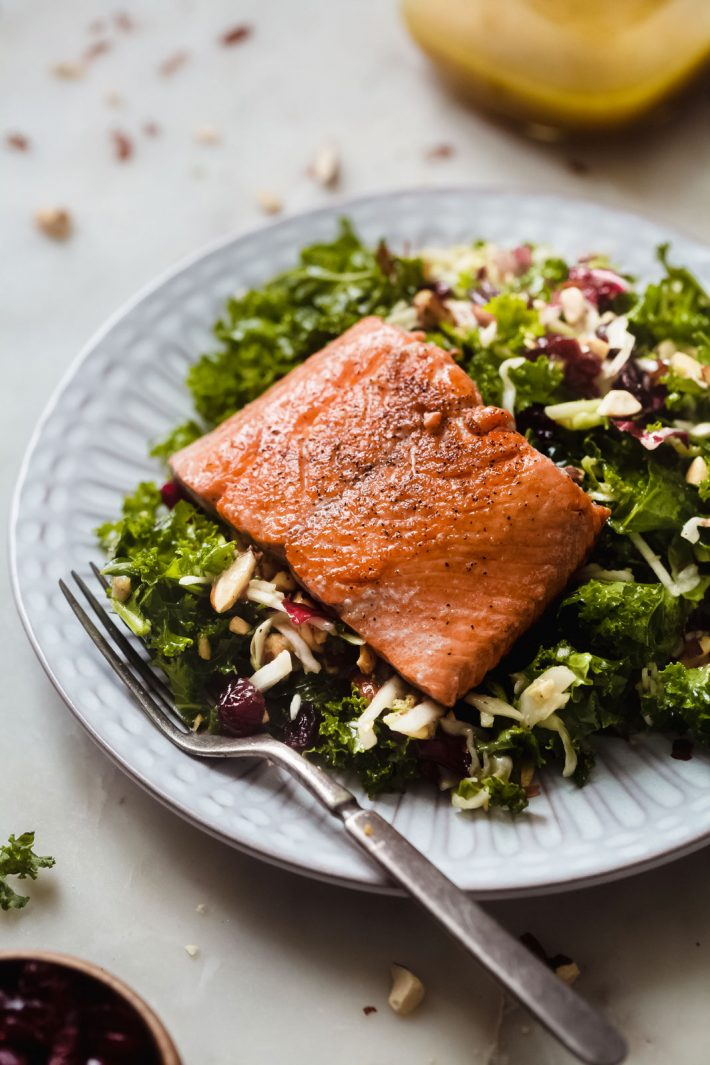 white fluted plate with dressed kale crunch salad topped with pan seared salmon filet