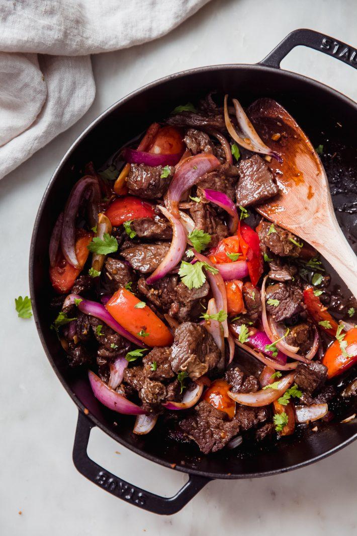 prepared Peruvian steak stir fry in black cast iron braiser