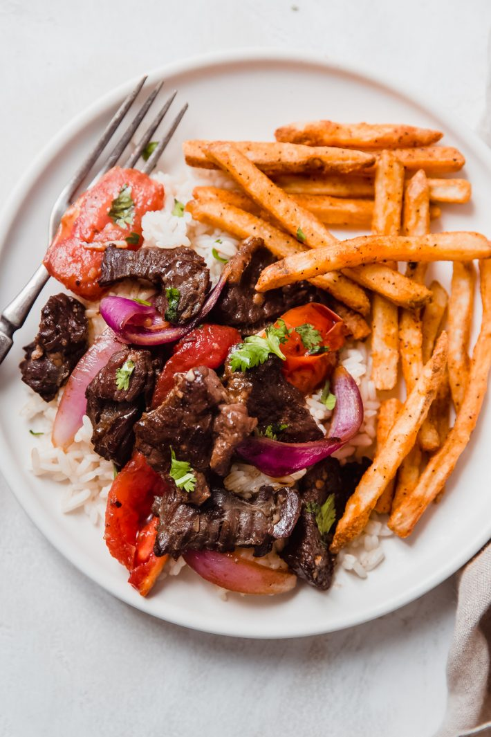lomo saltado over rice with French fries on the side on white plate