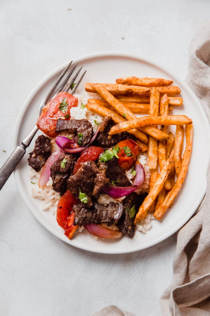 prepared plate of Lomo Saltado with rice and French fries on the side on grey surface