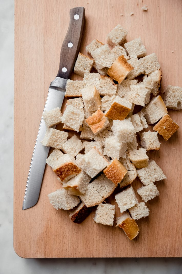 cubed bread on cutting board with knife