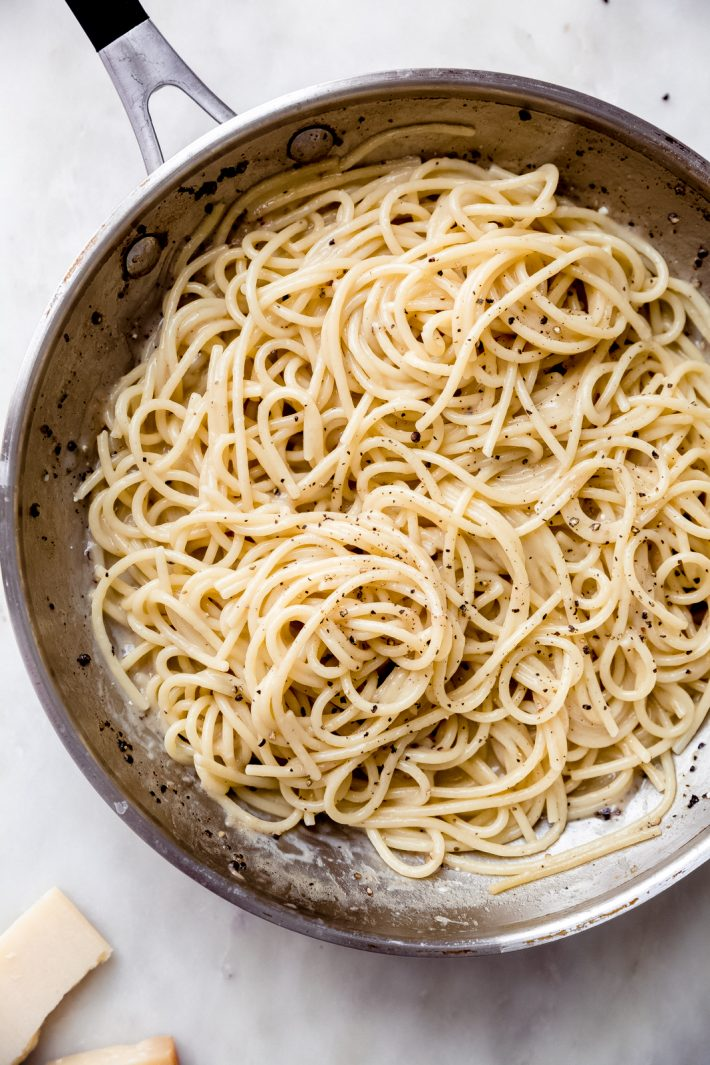 steel skillet with prepared spaghetti cacio e pepe sprinkled with coarse black pepper
