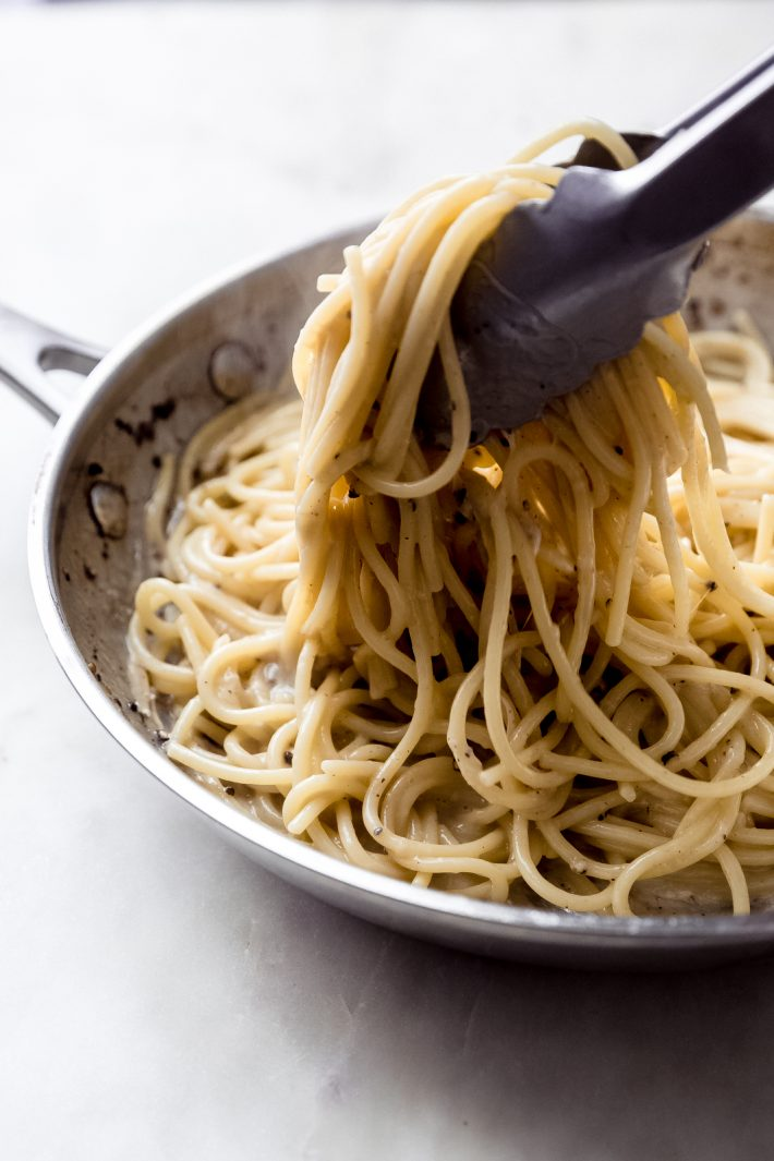 tongs lifting spaghetti from skillet