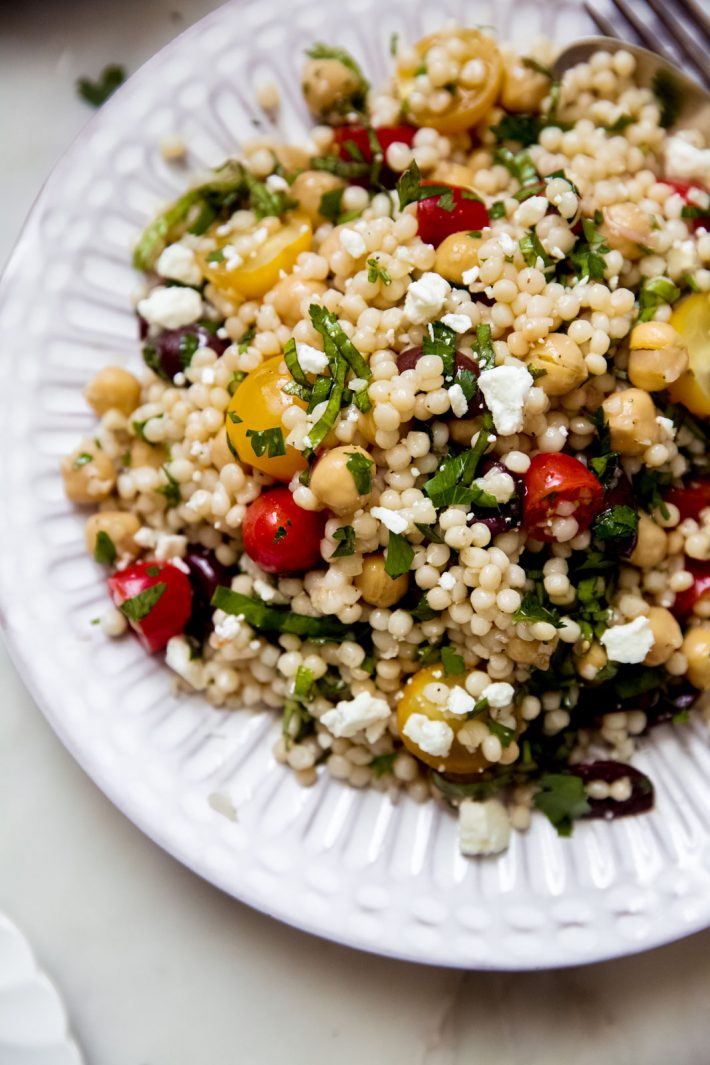 fluted plate with a close up of Israeli couscous salad with feta cheese and fresh tomatoes