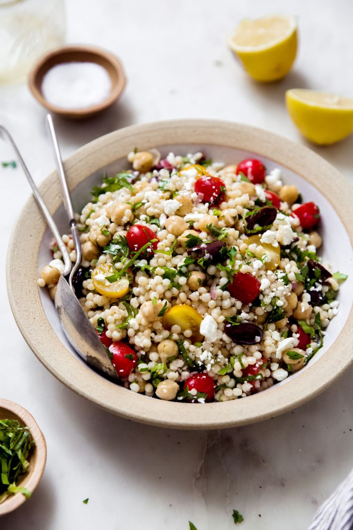rimmed plate with prepared Israeli couscous chickpea salad
