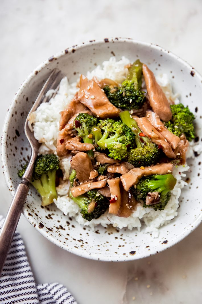 specked bowl filled with rice topped with chicken broccoli stir fry