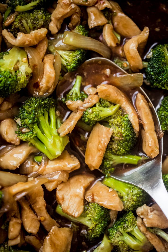 metal spoon holding prepared stir fry in skillet showing chicken, broccoli, and sauce