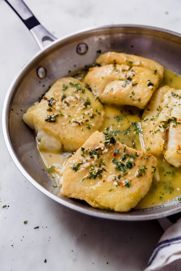 stainless steel skillet with pan-fried fish topped with lemon butter