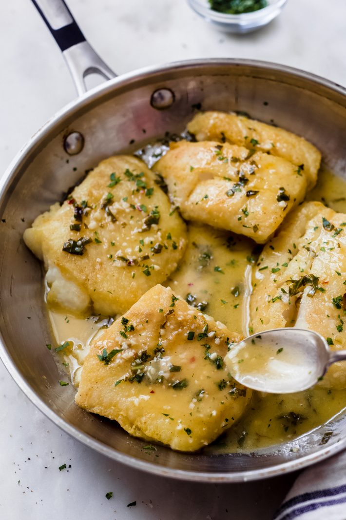 spoon pouring sauce over fish filet in skillet