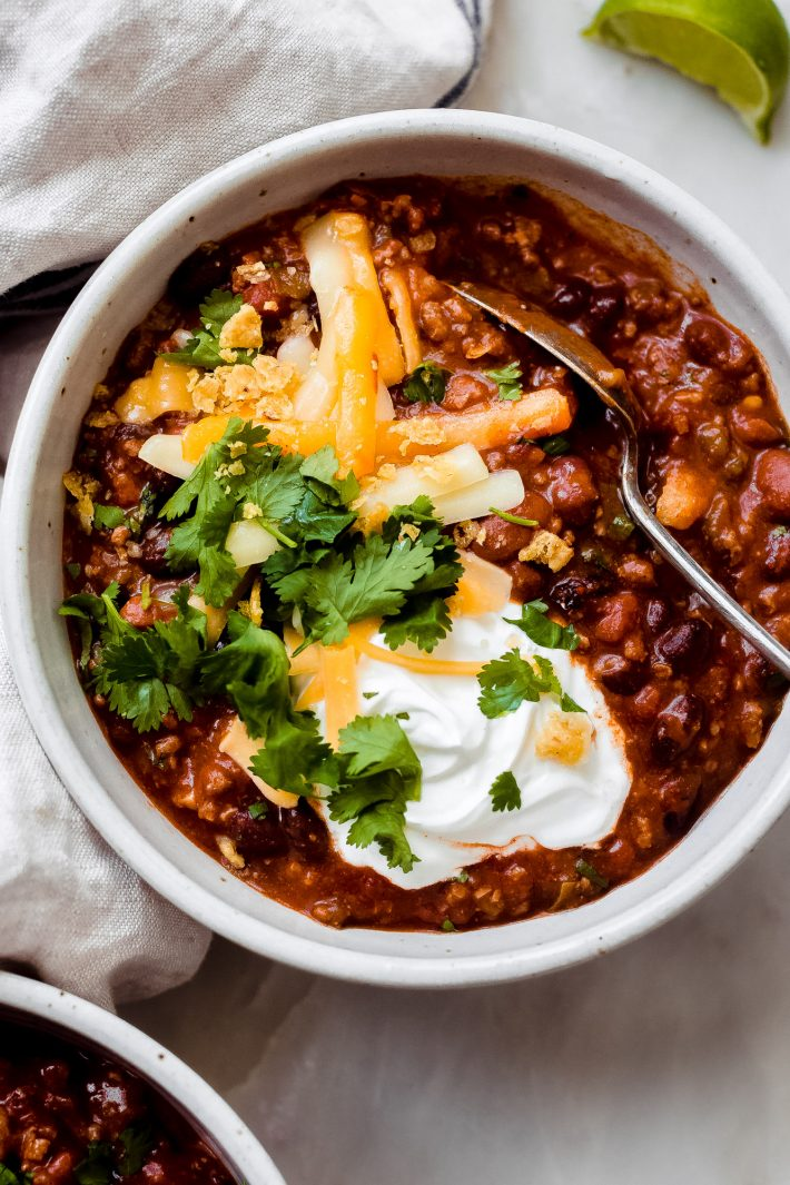 taco chili in bowl topped with shredded cheese, sour cream, and cilantro