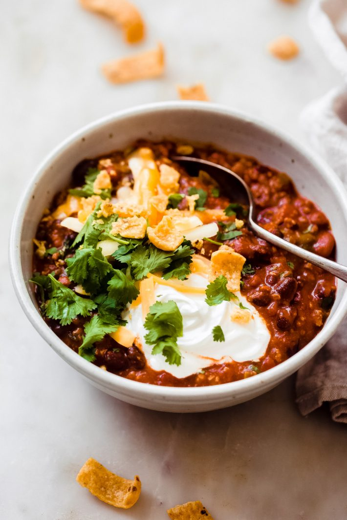 bowl to chili dressed with corn chips, sour cream, shredded cheese, and cilantro