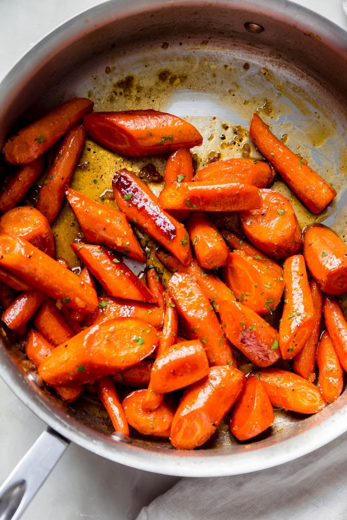 roasted carrots in saute pan tossed in sauce
