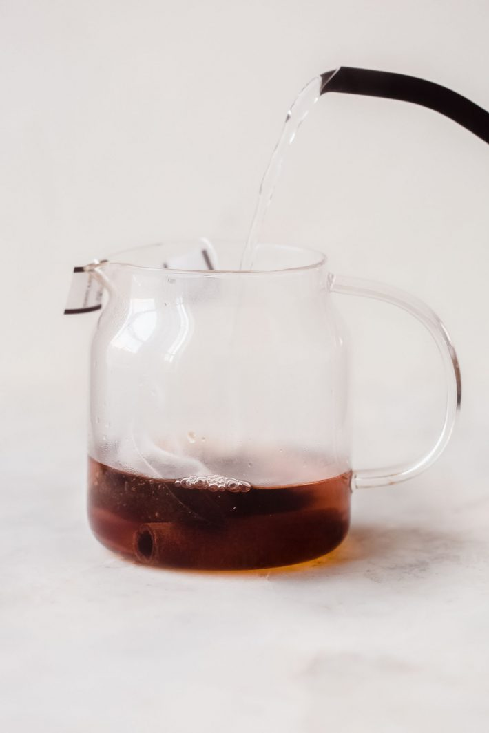 hot water being poured into glass tea pot with tea bags and cinnamon stick