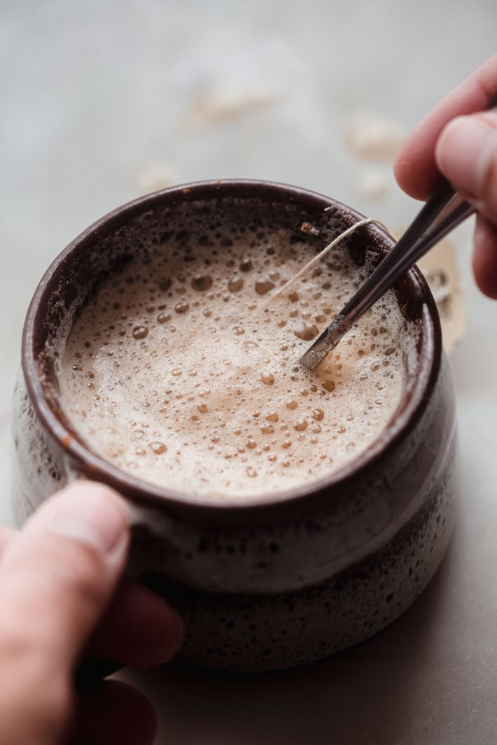 hand on mug and spoon stirring latte