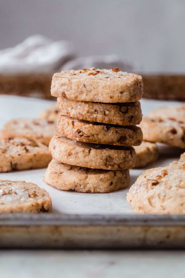 stack of cookies on baking sheet surrounded by more cookies