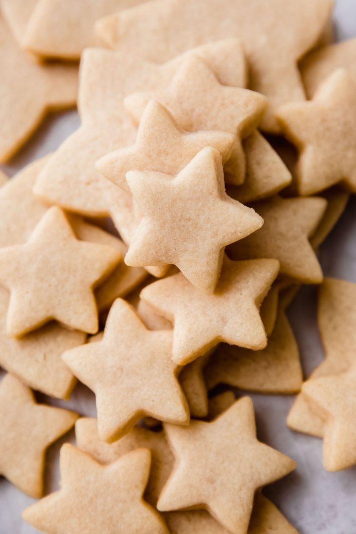 baked star shaped sugar cookies on white parchment