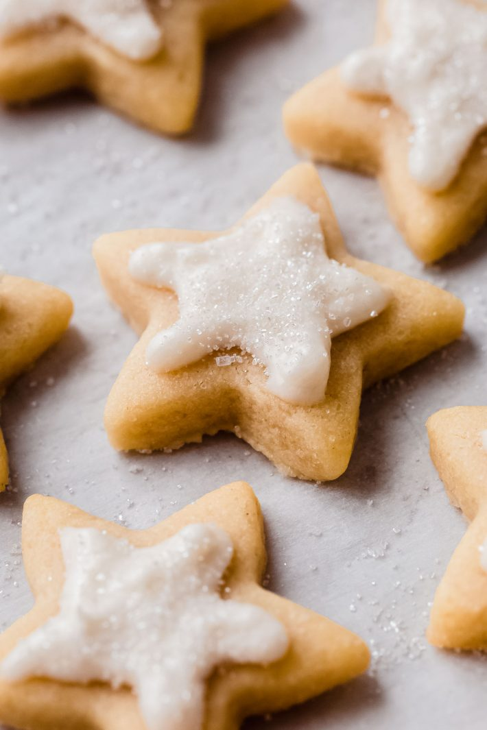 iced sugar cookies with with sprinkles on white parchment