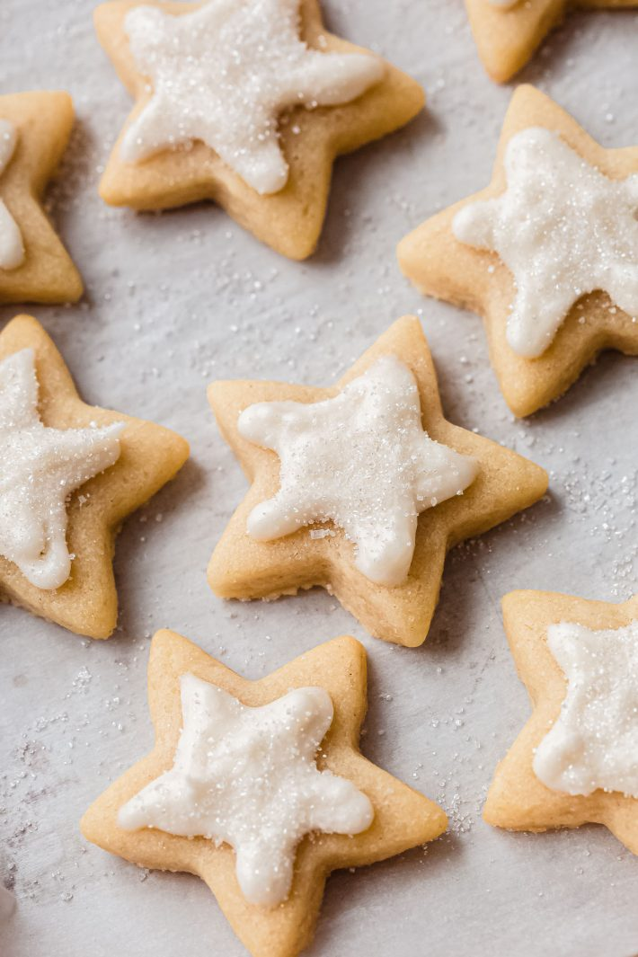 decorated star cut out sugar cookies on white parchment