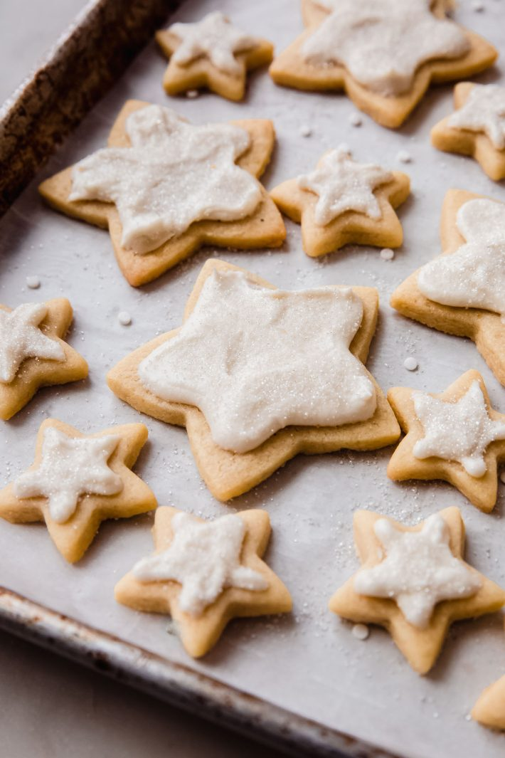 baking sheet filled with star shaped frosted cookies