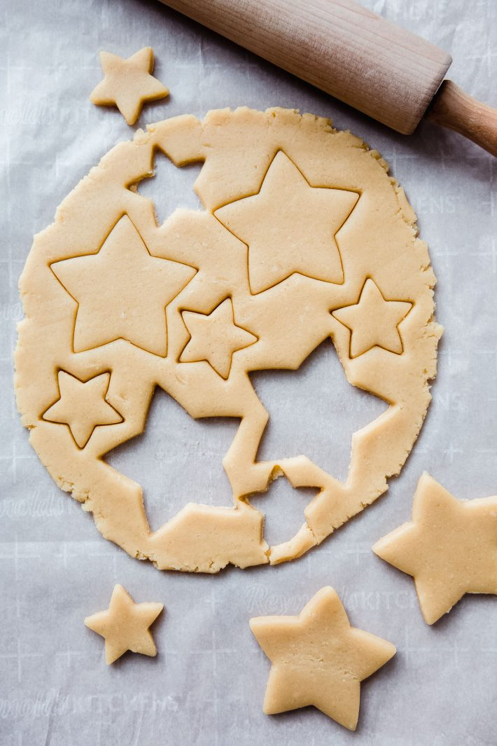 stars cut out of cookie dough with rolling pin on white parchment paper