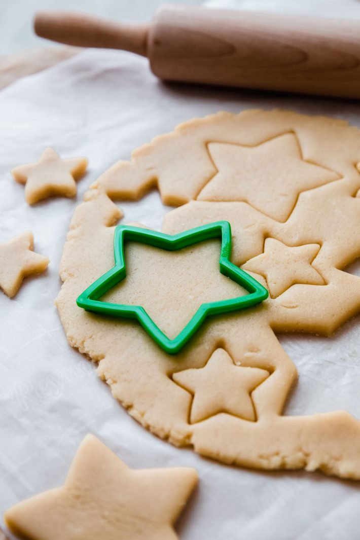 sugar cookie dough with star cut out on white parchment