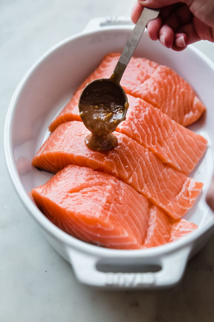 pouring miso ginger marinade over salmon fillets