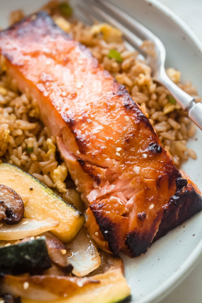 close up of broiled salmon fillet in plate over rice