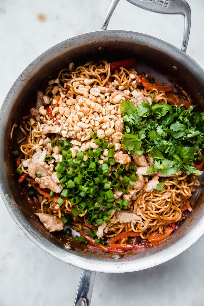 noodles in pan topped with chopped peanuts, green onions, cilantro before tossing